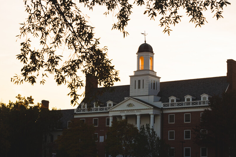 View of Anne Arundel Hall dormitory steeple at dusk with fall foliage.